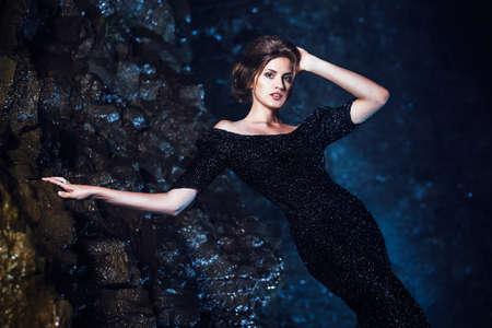 shiny black: Woman posing near waterfall