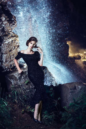 Woman posing near waterfall  photo