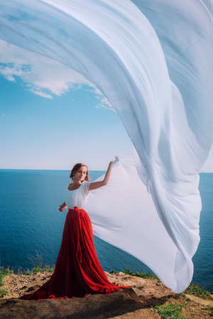 Beautiful Girl With White fabric on sea background photo