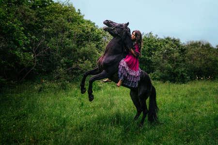 gitana: Hermosa mujer en un caballo vestidos con vestido violeta largo Foto de archivo