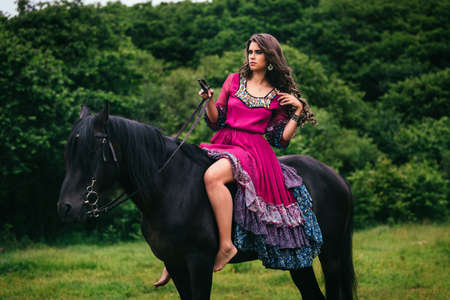 Beautiful woman on a horse dressed in long violet dress Stock Photo