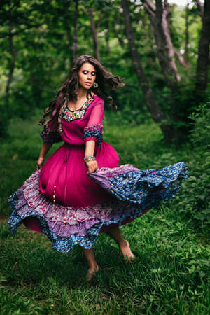 Portrait of a beautiful girl gypsy in violet dress 스톡 콘텐츠