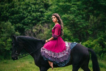 femme et cheval: Belle femme sur un cheval habillé en robe longue violette Banque d'images