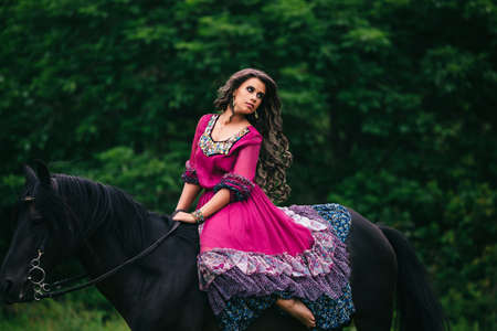 animal farm: Beautiful woman on a horse dressed in long violet dress Stock Photo