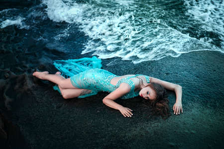 Fashionable woman posing on a beach with rocks in a long dress 스톡 콘텐츠
