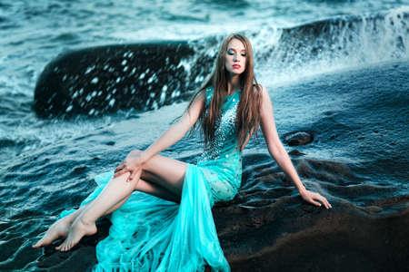 sexy young girl: Модная женщина позирует на пляже с камнями в длинном платье