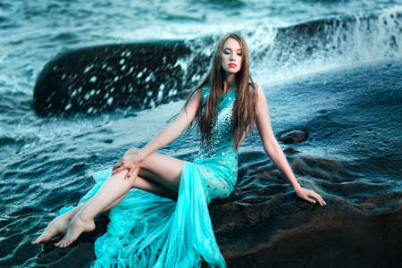 sea nymph: Fashionable woman posing on a beach with rocks in a long dress Stock Photo
