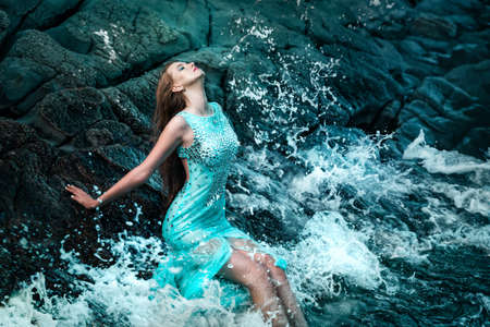 adult mermaid: Fashionable woman posing on a beach with rocks in a long dress Stock Photo