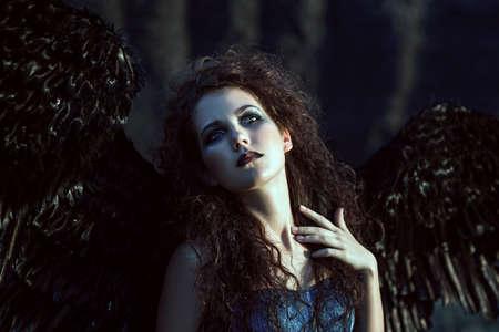 Mooi meisje-demon met zwarte vleugels achter haar rug Stockfoto