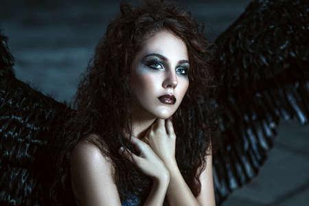 demonio: Muchacha bonita-demonio con alas negras detrás de la espalda