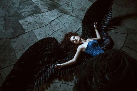 Muchacha bonita-demonio con alas negras detrás de la espalda