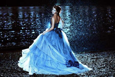 Schöne Dame im blauen Kleid zu Fuß in der Nähe von Meer