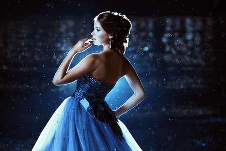 Beautiful lady in blue dress walking near sea