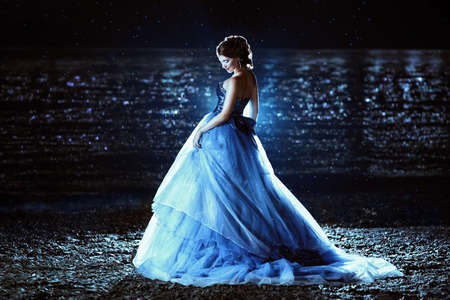 blue sea: Beautiful lady in blue dress walking near sea