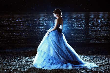 vestido de noche: Bella dama en vestido azul caminando cerca del mar