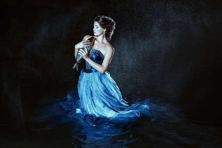animal woman: Beautiful lady in blue dress walking near sea
