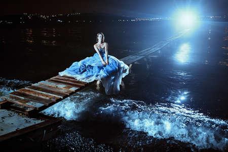 gown: Beautiful lady in blue dress walking near sea