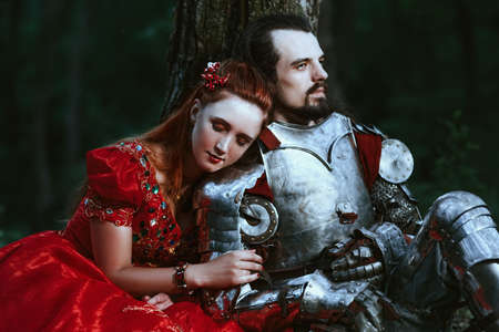 medieval king: Medieval knight with his beloved lady in red dress Stock Photo