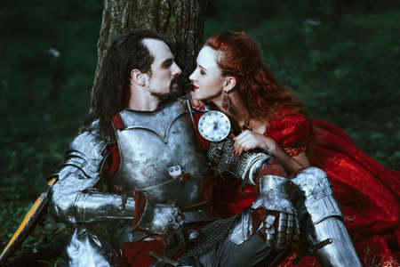 medieval woman: Medieval knight with his beloved lady in red dress Stock Photo