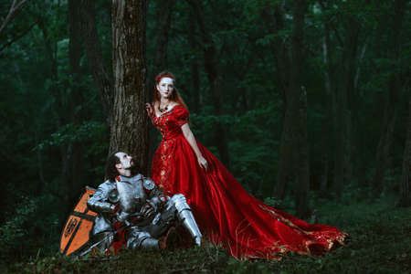 beloved: Medieval knight with his beloved lady in red dress Stock Photo