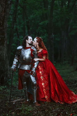 femme romantique: Medieval knight with his beloved lady in red dress Banque d'images