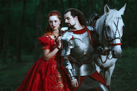 medieval sword: Medieval knight with his beloved lady in red dress Stock Photo