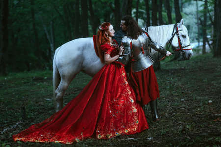 Medieval knight with his beloved lady in red dress 写真素材