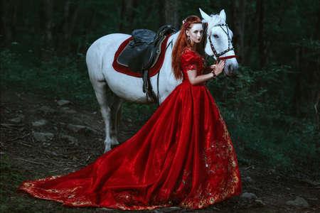 femme a cheval: Princesse en robe robe rouge à cheval dans la forêt Banque d'images