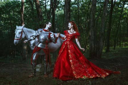 Medieval knight with his beloved lady in red dress Stockfoto