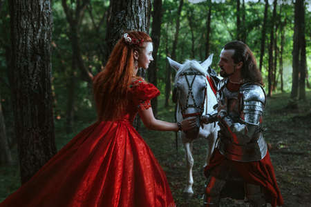 woman with sword: Medieval knight with his beloved lady in red dress Stock Photo