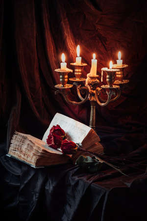 Still life with skull, dry roses, antique book and candlestick