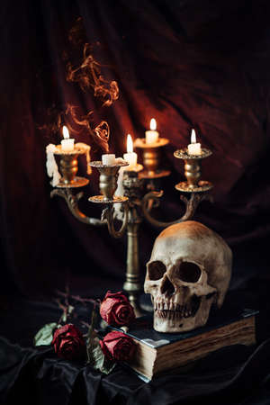 manuscript: Human skull on book with antique candlestick. Still life