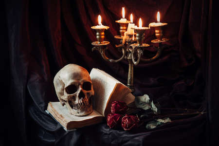 Human skull on book with antique candlestick. Still life