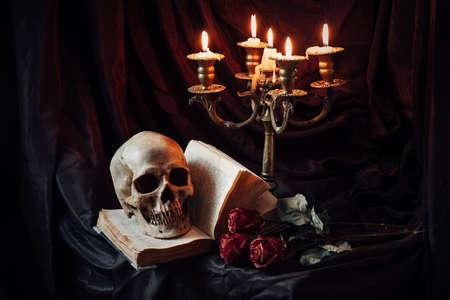 Menschlicher Schädel auf Buch mit antiken Leuchter. Stillleben Standard-Bild