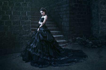石の壁に近い黒のドレスで魅力的な女性 写真素材