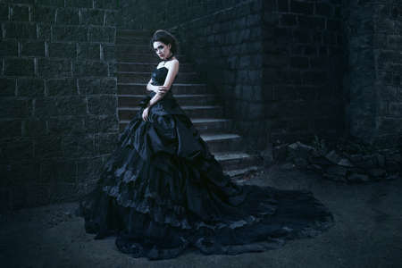 Attractive woman in black dress near stone wall Фото со стока - 54746849
