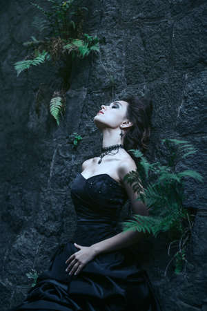 satanist: Shoot of  sad brunette over the ancient building background Stock Photo