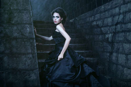 Aantrekkelijke vrouw in zwarte jurk in de buurt van stenen muur