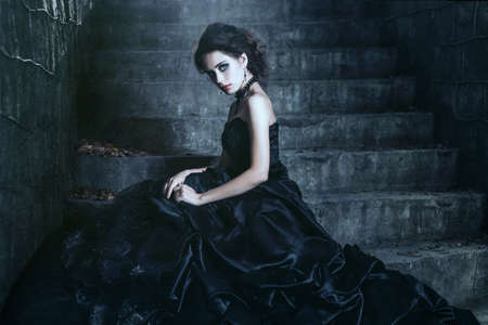 gothic girl: Shoot of  sad brunette over the ancient building background Stock Photo