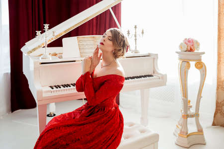 red evening: A young beautiful woman in a red evening dress sits at the grand piano Stock Photo