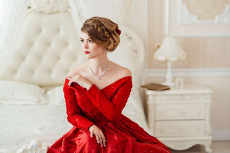 engagements: Beautiful woman in a red dress lying on bed.
