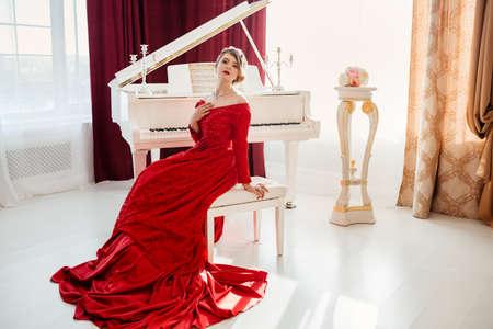 anochecer: Una mujer joven y bella en un vestido de noche rojo se encuentra en el piano de cola