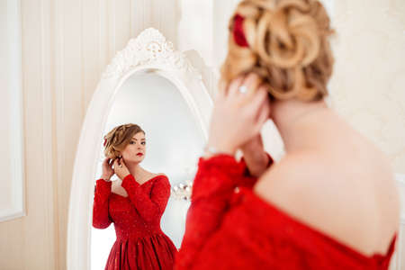 Woman dressed in red dress looking in mirror