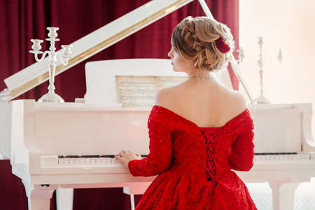 A young beautiful woman in a red evening dress sits at the grand piano Stock Photo