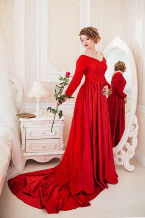 girl in red dress: Woman dressed in red dress standing near mirror Stock Photo
