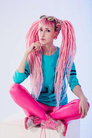 rastas: adolescente moderna con rastas de color rosa sobre fondo blanco