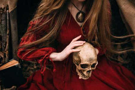 秋の森で赤いドレスの若い女性