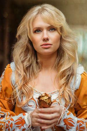 Piękne blond kobieta w średniowiecznej sukni spaceru w pobliżu starego budynku