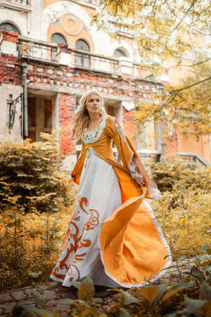 오래 된 건물 근처 중세 드레스 산책 아름 다운 금발 여자 스톡 콘텐츠 - 60901151
