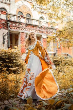 hermosa mujer rubia en traje medieval a pie cerca del edificio viejo